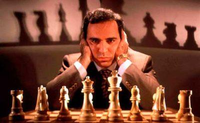 Garry Kasparov mirando de frente con sus manos en la cabeza posando con un tablero de ajedrez