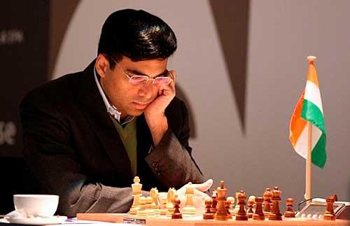 Viswanathan Anand pensando en un tablero de ajedrez tomando un cafe en un taza y con una bandera de india a su izquierda