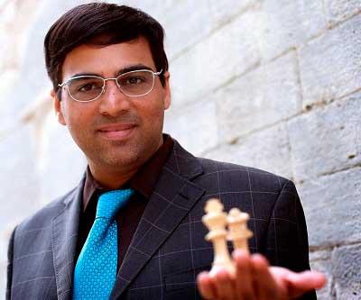 Viswanathan Anand posando en foto de frente sujetando dos piezas de ajedrez en su mano izquierda rey y dama